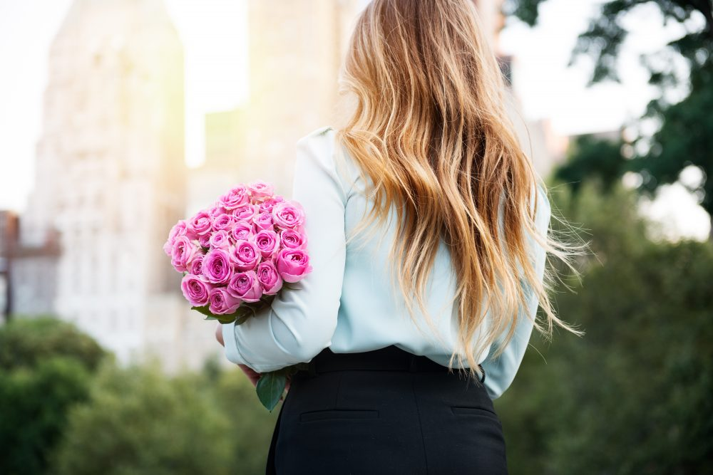 Beautiful girl holding bouquet of pink roses flowers on dating
